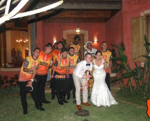 Noivos animados com a chegada da escola de samba